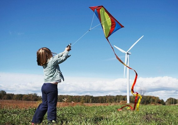 Toronto, Ontario, Canada --- Girl flying kite at wind farm --- Image by © Darren Kemper/Corbis